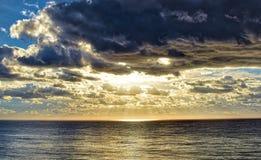 Rain cloud over Ocean. Sun shining through thick rain cloud over the ocean, Costa Azul, Baja California, Mexico royalty free stock photo
