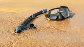 Sun shining to black snorkel and diving mask on wet beach sand, washed by sea royalty free stock photos