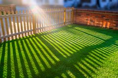 Sun shining through a wooden picket fence onto an artifical gras. Sunshine creating lens flare through a wooden picket fence in a front yard, front garden with Royalty Free Stock Photography