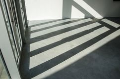 Shadow by door and window. The sun shone through the glass doors and windows, and shadows fell on the ground Stock Photo