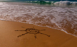 Sun sign drawn on sand of beach Royalty Free Stock Image
