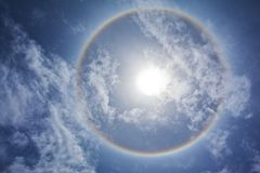 Sun with sircular rainbow and clouds royalty free stock photo