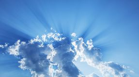 Sun slanting among from white clouds. Nature background Royalty Free Stock Image