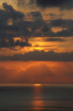 Sun slowly dipping in the ocean, covered by thin, indecisive clouds. Vertical shot of a perfect sunset with clouds like a pot of molten lava, over Atlantic Stock Photo