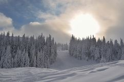 Sun and snow. Sun behind clouds in winter mountains royalty free stock photography
