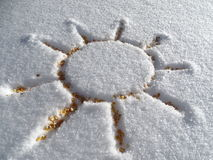 Sun and snow once a friend. In the Photo is the sun, which is drew in the snow. In the drawed sun are grains of maize. Corn grains are actually yellow like the Stock Photos