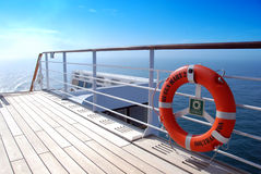 Sun-soaked deck of QM 2. Orange lifebelt and teak deck under an azure blue sky aboard ocean liner Queen Mary 2 Royalty Free Stock Photography