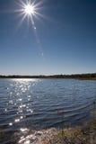 Sun sobre el lago con la flama de la lente Imagen de archivo