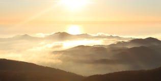 Sun sobre montanhas e nuvens Imagens de Stock