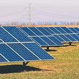 Sun and solar panels in a field. Solar energy power plant. Industrial and ecological concept for nature and eco / green technology Royalty Free Stock Photography