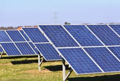 Sun and solar panels in a field. Solar energy power plant. Industrial and ecological concept for nature and eco / green technology Royalty Free Stock Photos