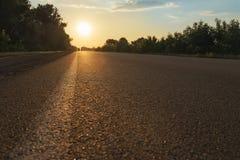 Sun sopra la strada asfaltata Immagine Stock