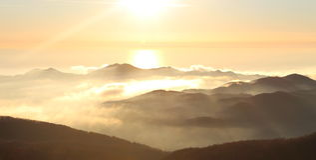 Sun sopra le montagne e le nuvole Immagini Stock