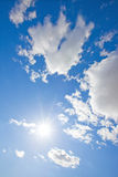 Sun sparkling in blue sky with fluffy clouds Stock Photo