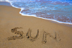 Sun spell written work in sand of a beach Stock Images