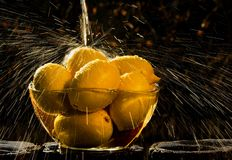 Sun spray. Drops of water flying in the sunlight as they fall on the lemons stock photography