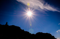 Sun Star on a Blue Sky over a Mountain Silhouette. In Gran Canaria Spain Stock Photo