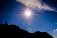 Sun Star on a Blue Sky over a Mountain Silhouette Stock Photo