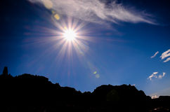 Sun Star on a Blue Sky over a Mountain Silhouette Royalty Free Stock Photo