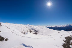 Sun star glowing over snowcapped mountain range and high mountain peaks in the italian alpine arc, in a bright sunny day of winter Stock Photography