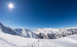 Sun star glowing over snowcapped mountain range, italian Alps Royalty Free Stock Photography