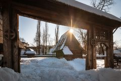 Sun star warming up a traditional Romanian homestead in winter Royalty Free Stock Images