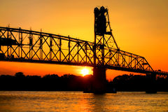 Sun by Steel Bridge Silhouette on River at Sunset Royalty Free Stock Photo