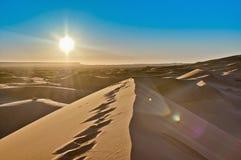 Sun steigt über Erg Chebbi bei Marokko stockbild