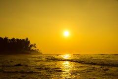Sun stellt auf Horizont bei Sonnenuntergang ein Sonnenaufgang über Meer oder Ozean Lizenzfreie Stockbilder