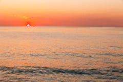 Sun stellt auf Horizont bei Sonnenuntergang-Sonnenaufgang über Meer oder Ozean ein T stockfoto