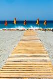 Sun stolar med paraplyer på stranden Arkivbilder