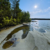 Sun and stony shore of Ladoga lake Stock Photo
