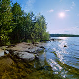 Sun and stony shore of Ladoga lake Stock Photography
