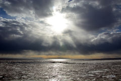 Sun through the stormy clouds at the frozen sea Stock Image