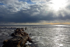 Sun through the stormy clouds at the frozen sea. With broken ice Stock Photo