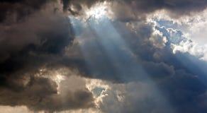 Sun strålar till och med stormmoln Arkivbild