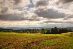 Sun strahlt das Glänzen durch die Wolken auf Landschaft aus Stockfoto
