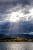 Sun strahlt das Glänzen durch Wolken auf den Hügeln von See Jindabyne aus, stockfoto