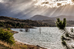 Sun strahlt das Glänzen durch Wolken auf den Hügeln von See Jindabyne aus, stockbilder