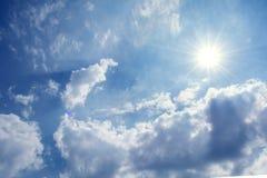Sun strahlt gegen einen blauen Himmel in den Wolken aus, Lizenzfreie Stockfotografie