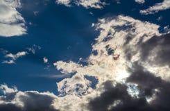 Sun strahlt gegen einen blauen Himmel in den Wolken aus Stockfoto