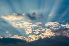 Sun strahlt gegen einen blauen Himmel in den Wolken aus Stockbilder