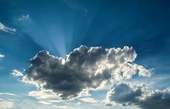 Sun strahlt gegen einen blauen Himmel in den Wolken aus Lizenzfreies Stockfoto