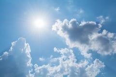 Sun strahlt gegen einen blauen Himmel in den Wolken aus Lizenzfreie Stockbilder
