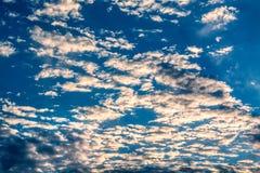 Sun strahlt gegen einen blauen Himmel in den Wolken aus Lizenzfreie Stockfotos