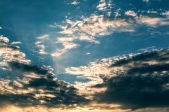 Sun strahlt gegen einen blauen Himmel in den Wolken aus Stockfotos