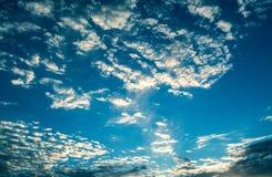 Sun strahlt gegen einen blauen Himmel in den Wolken aus Lizenzfreie Stockfotografie