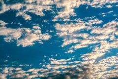 Sun strahlt gegen einen blauen Himmel in den Wolken aus Stockfotografie