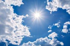 Sun strahlt gegen einen blauen Himmel in den Wolken aus, Stockfotografie