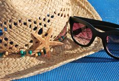 Sun straw hat with beads and decoration starfish and sunglasses Royalty Free Stock Image